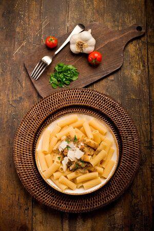 comida italiana: deliciosos macarrones de pasta con pesto siciliano en la mesa de madera