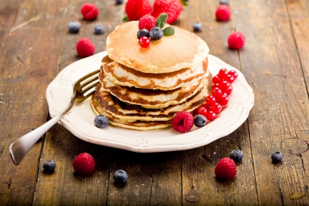 hotcakes: delicious pancakes on wooden table with fruits  Stock Photo