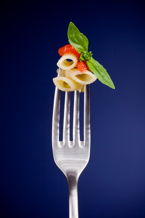 delicious italian pasta with tomato sauce and basil on fork over blue background