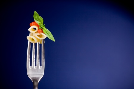 pasta salad: delicious italian pasta with tomato sauce and basil on fork over blue background