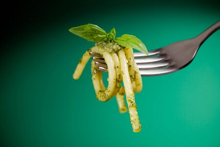 pasta fork: photo of italian bucatini pasta with pesto wrapped on a fork