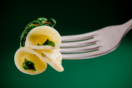 Italian Regional dish with pasta and turnip tops holded by a fork