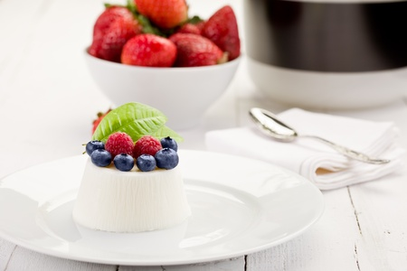 panna cotta: photo of delicious panna cotta with berries on white wooden table Stock Photo