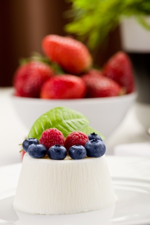 photo of delicious panna cotta with berries on white wooden table photo