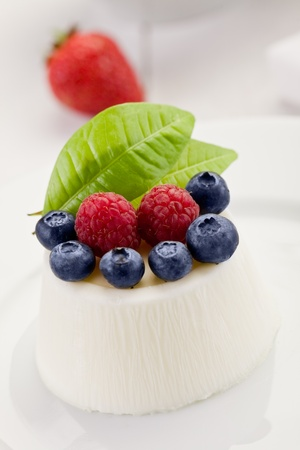 photo of delicious panna cotta with berries on whitetable photo