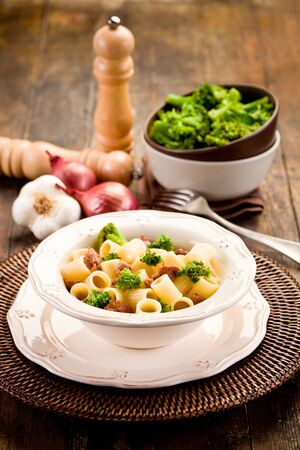 photo of delicious pasta with sausage and broccoli on wooden table photo