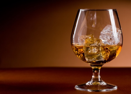 drunkenness: photo of delicious glass of cognac whiskey with ice cubes on brown background Stock Photo