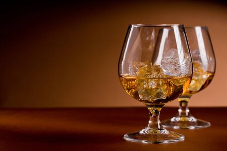 cognac: photo of delicious glass of cognac whiskey with ice cubes on brown background Stock Photo