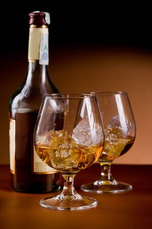 liqueur bottle: photo of delicious glass of cognac whiskey with ice cubes on brown background Stock Photo