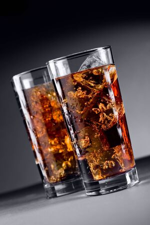 Photo of delicious cold glass with cola and ice cubes photo