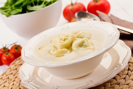 delicious tortellini pasta in broth with vegetables on white table  photo
