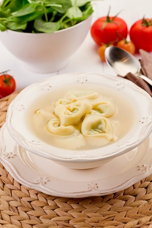stuffed tortellini: delicious tortellini pasta in broth with vegetables on white table