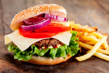 photo of delicious hamburger with fries on wooden table   photo