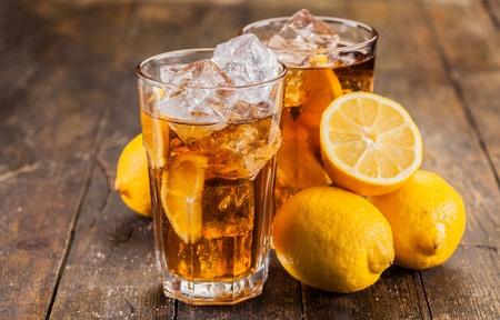 ice lemon tea: lemon ice tea on brown wooden table with lemons around Stock Photo