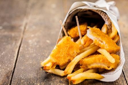 pescado frito: Deliciosos pescados y papas fritas en el cono de periódico tradicional