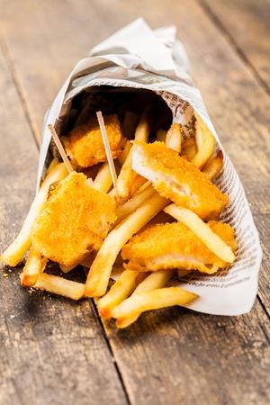 fish and chips: Delicioso pescado y patatas fritas en cono periódico tradicional