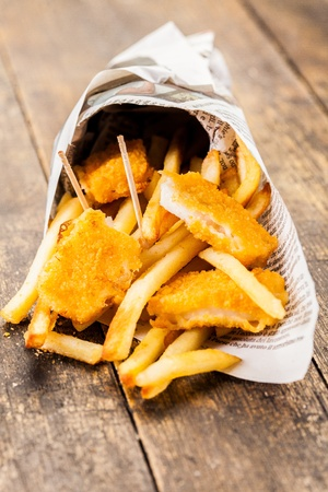 golden fish: Delicious fish and chips in traditional newspaper cone  Stock Photo