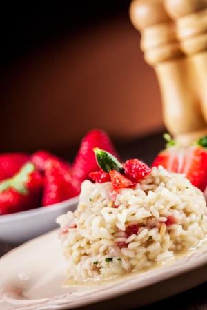 Delicious risotto with strawberries on wooden table photo