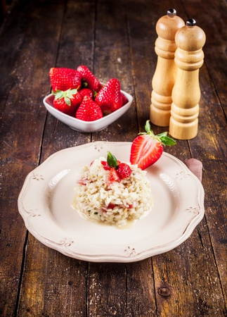 rice mill: Delicious risotto with strawberries on wooden table Stock Photo