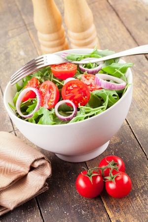 トマトとオニオン リング木製のテーブルでおいしい光ルッコラのサラダ