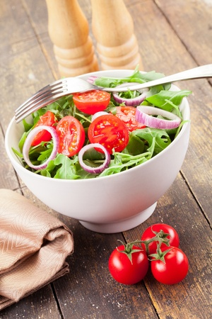 Delicious light arugula salad with tomatoes and onion rings on wooden table Standard-Bild