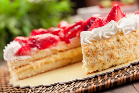 delicious strawberry cake with cream on wooden table photo
