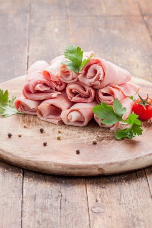 delicious raw ham rolls on wooden table with parsley leaves