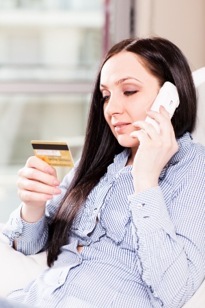 beautiful girl with credit card in her hands is buying something via phone photo