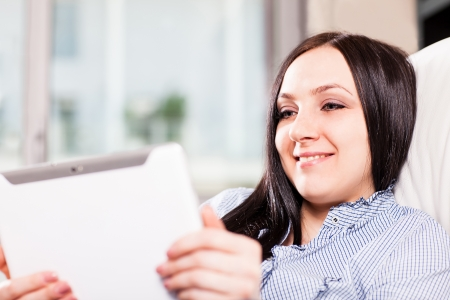 Beautiful woman at home is smiling while videocalling with a tablet photo