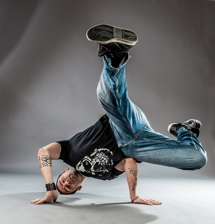 pohto of break dancer who is performing his dance on the floor  photo