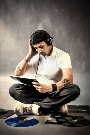 photo of dj with vinyls on the floor listening his music photo
