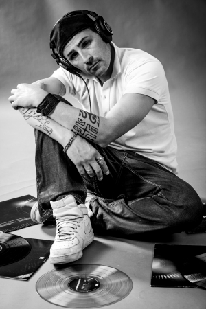 Black and white portrait of a dj sitting on the floor with vinyls  photo