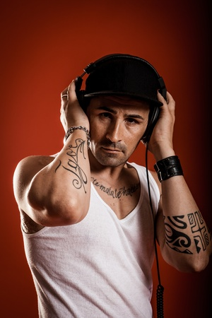 DJ with Scarfs and tatoos in front of a red background   photo