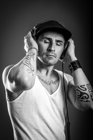 tatoos: black and white photo of man with tatoos who is listening to music