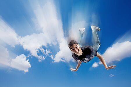 Boy is falling through the clouds while showing funny face