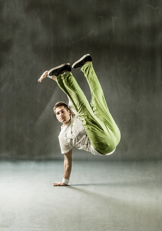 image of a dancer making his movements on grey background photo