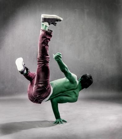 break dance: photo of green alien who is break dancing on the floor perfornming a freeze