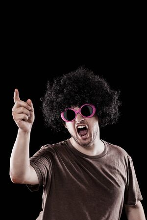 Man with funny sunglasses is grooving over black background Stock Photo - 14199166