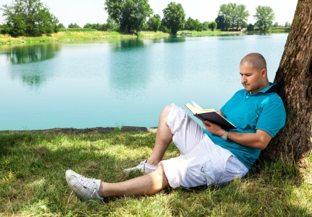 man is sitting outside in a park with lake and reading a book photo