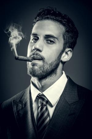 若い魅力的な実業家は、葉巻を吸っています。