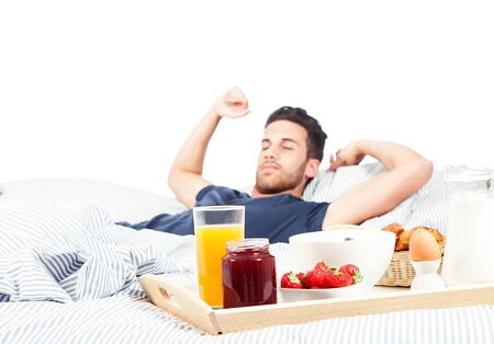 having breakfast: photo of adult man having breakfast in the bed on white background