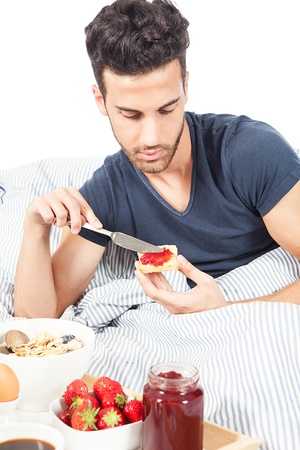 seed bed: photo of adult man having breakfast in the bed on white background