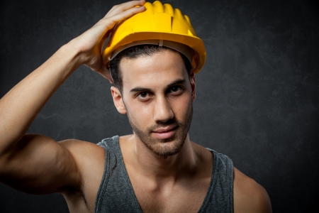 constructors: a male constructor with helmet over grey rural background
