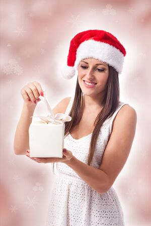 beautiful woman is opening a christmas gift photo