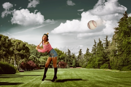 attractive girl is playing baseball in a park photo