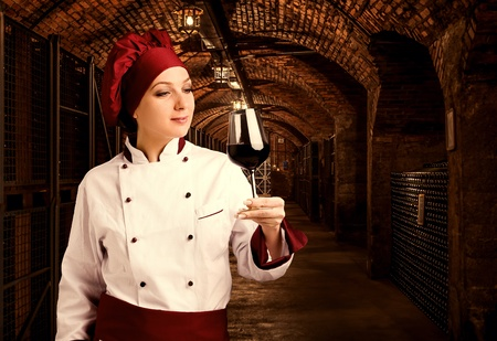 glass brick: Young female somelier is tasting her wine in a wine cellar Stock Photo