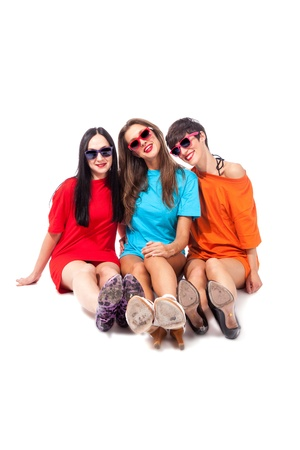 photo of three beautiful ladies sitting in front of a white background photo