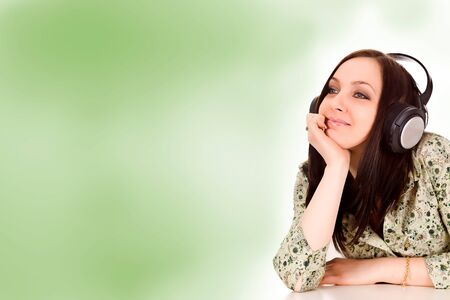 photo of attractive woman with headphones in front of a green background photo