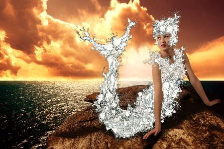 cola mujer: Mermaid está sentado sobre una roca durante una puesta de sol