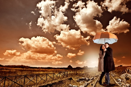 Couple under and umbrella is prepared and waiting for the storm photo